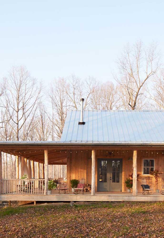 Casa de campo de madeira com varanda percorrendo toda lateral
