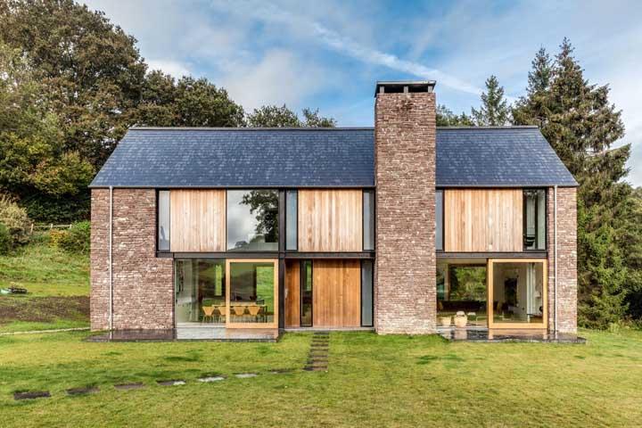 Casa de campo com fachada de pedra e um lindo gramado na frente