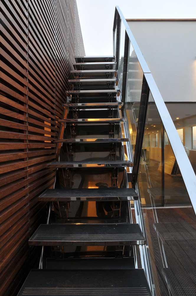 Degraus de ferro, corrimão de vidro e parede de madeira. Tem combinação mais perfeita?