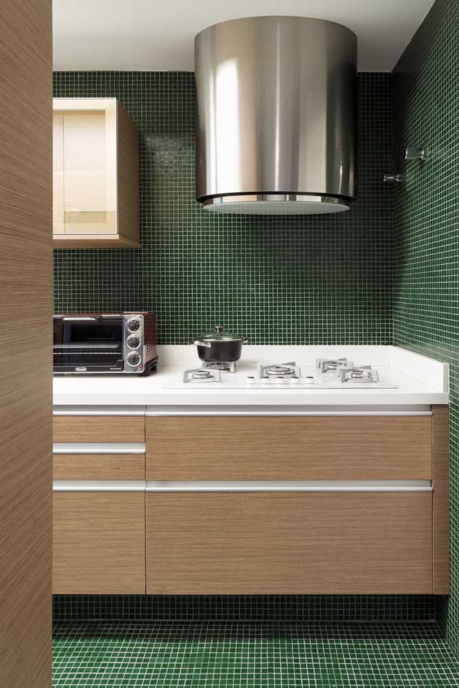 Que tal aplicar pastilhas no mesmo tom da parede até o piso da cozinha?