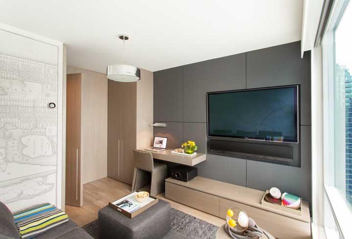 Brinque com papel de parede e revestimentos diferentes para harmonizar a sala de TV.