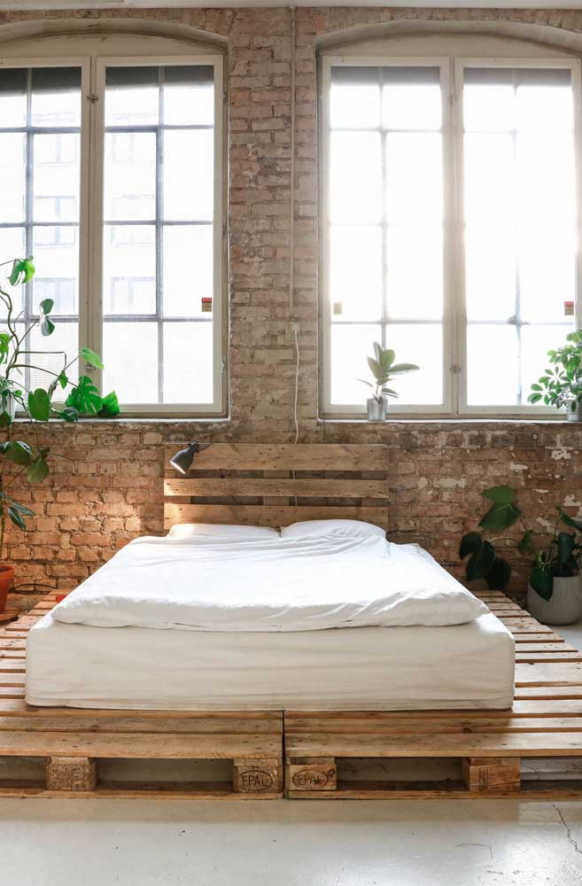 O quarto com parede de tijolinhos aceitou muito bem a cama e a cabeceira feita com pallets