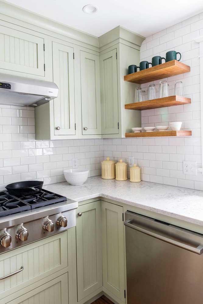 Cozinha vintage com azulejos de metrô e armário verde menta. As prateleiras garantem um charme extra ao ambiente