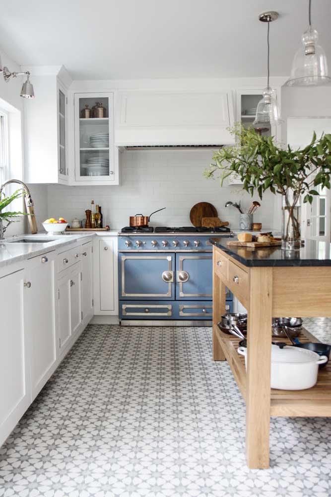 Cozinha vintage branca com piso vintage. Destaque para o fogão azul, uma peça cheia de histórias para contar