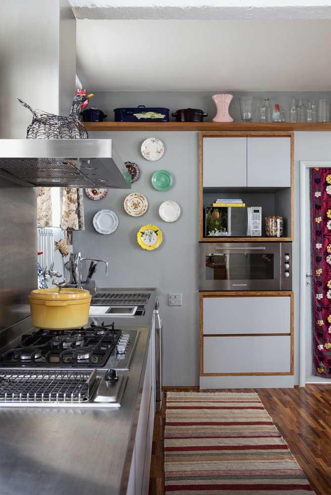 Nessa cozinha vintage, os pratos na parede e a passadeira no chão dividem espaço com a moderna bancada de inox