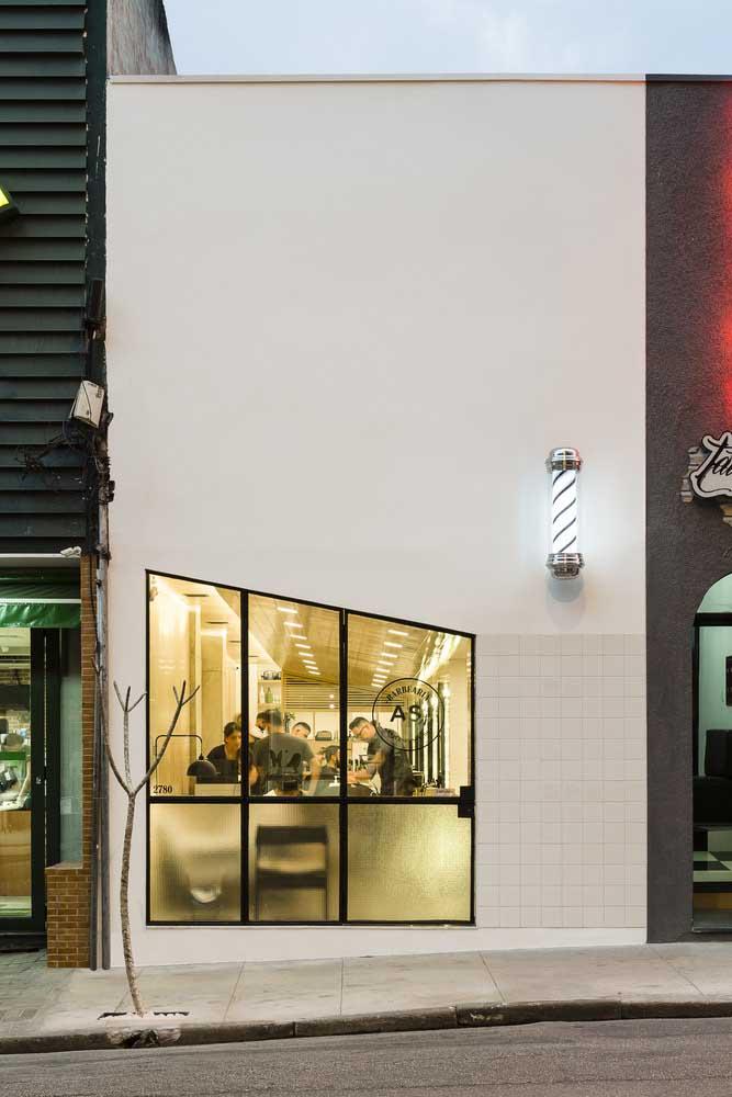 Fachada comercial simples, pequena e moderna com destaque para a porta de vidro que também funciona como vitrine