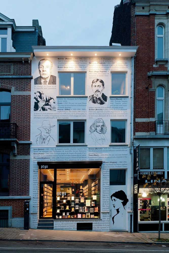 Linda inspiração de fachada de livraria. A parede de entrada ganhou páginas de livro e imagens de escritores. Tudo isso sem pesar no visual