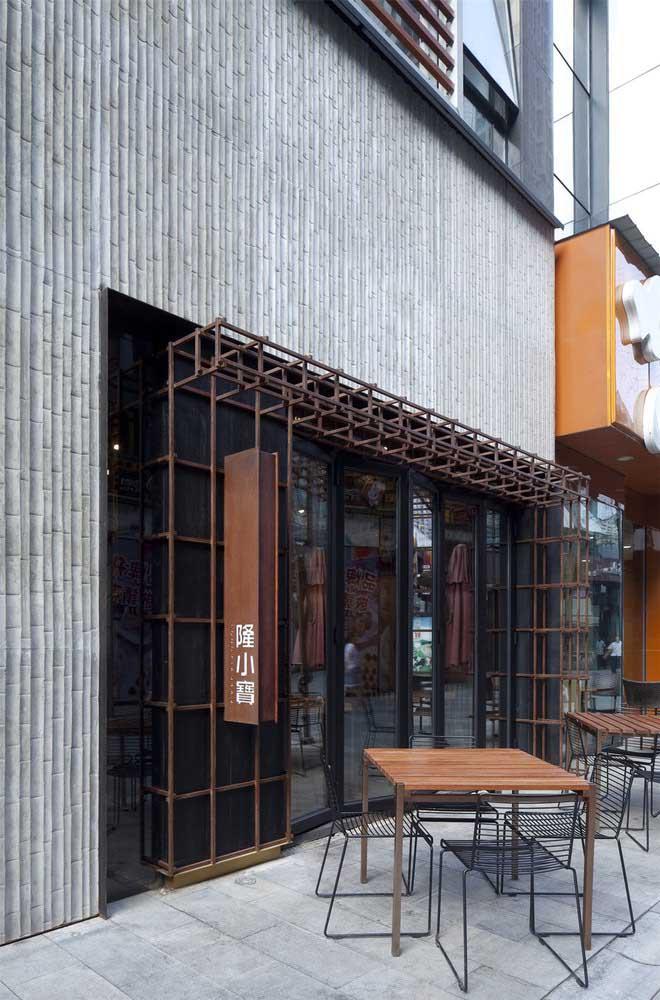 As mesas e cadeiras do lado de fora são um convite para quem passa por essa fachada comercial