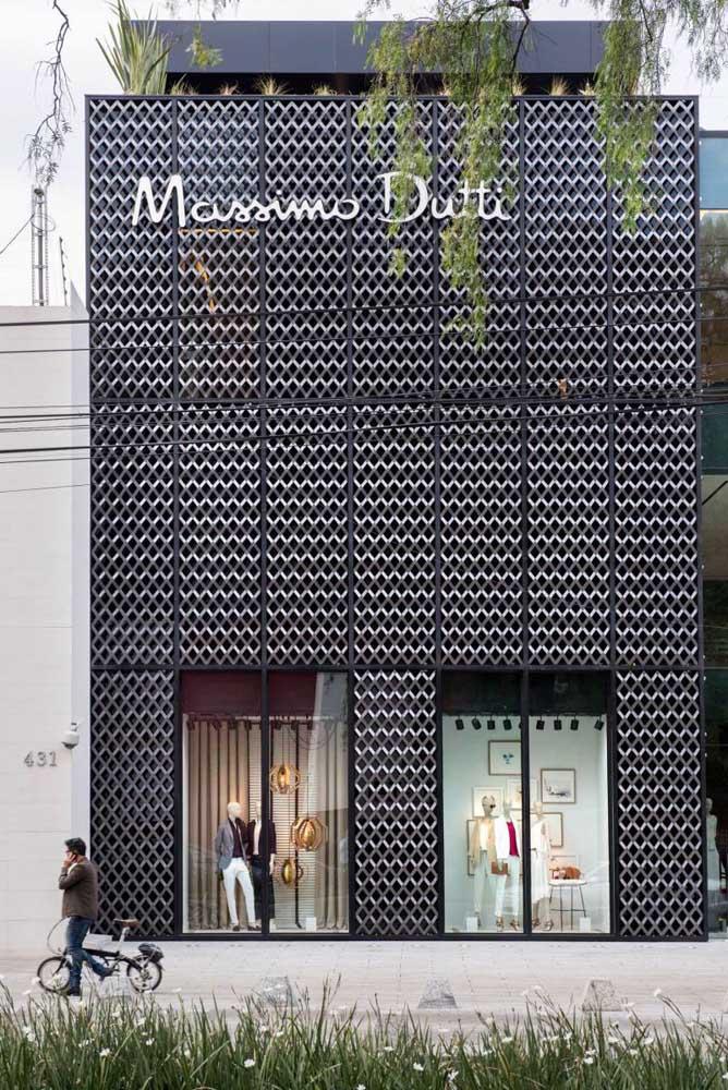 Fachada comercial moderna para loja de roupas. Destaque para o revestimento metálico que se contrapõem a vitrine