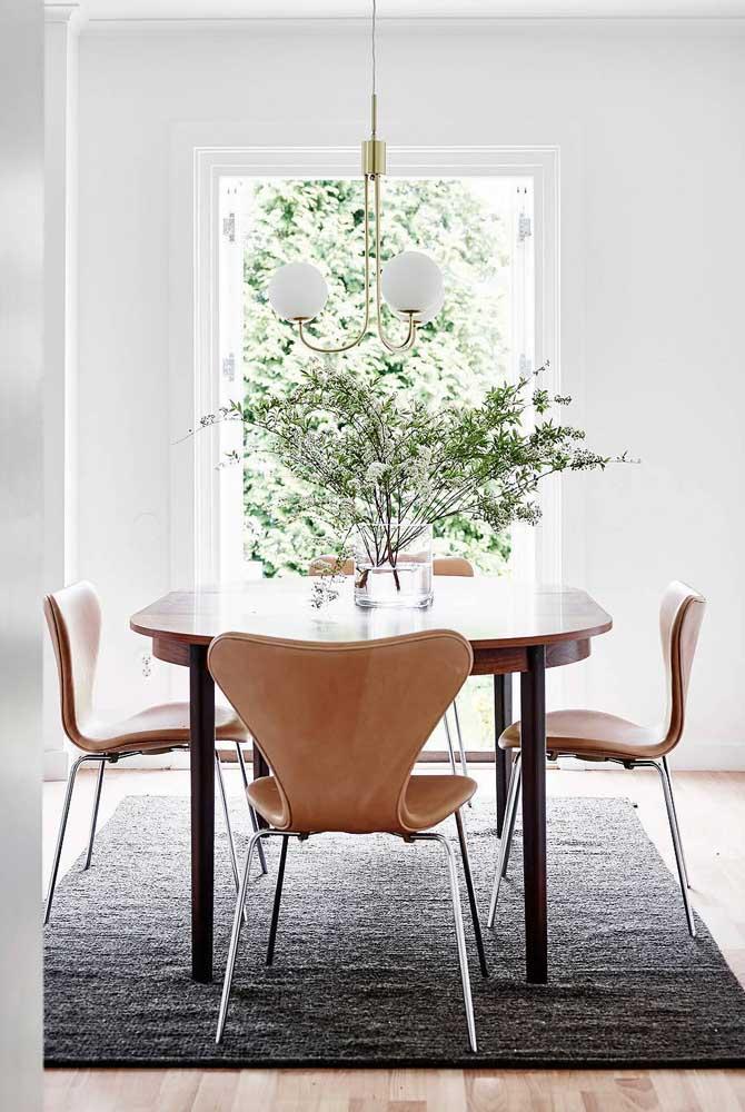 Um belo vaso com flores e mais o lustre deixam a sala de jantar mais charmosa.