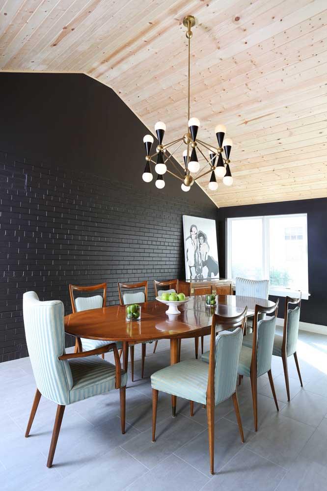 Olha o charme dessa sala de jantar com parede na cor preta e o lustre seguindo o mesmo estilo.