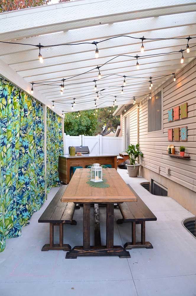 Área gourmet pequena e charmosa para você se inspirar. A cortina de chita e o varal de lâmpadas são um mimo à parte