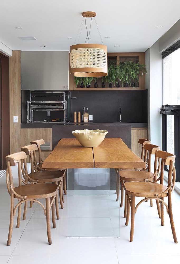A base de vidro da mesa ajuda a aumentar a sensação de espaço dessa área gourmet pequena