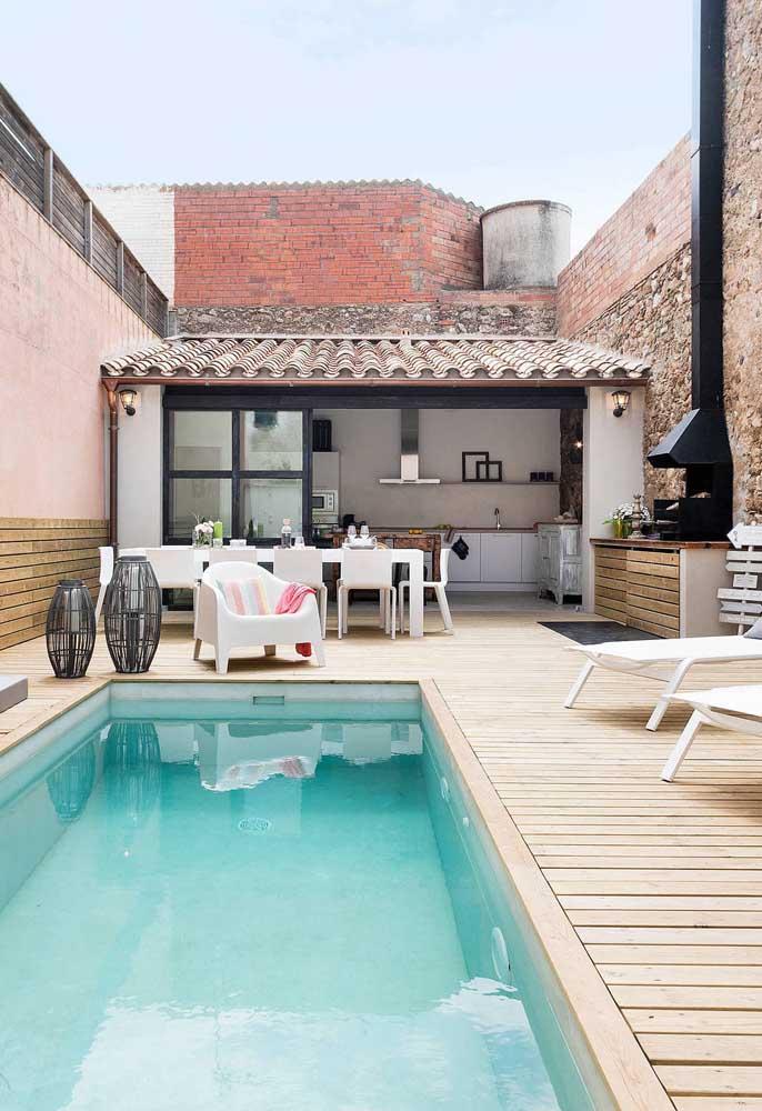 Área gourmet pequena e aconchegante com piscina para garantir a diversão da família