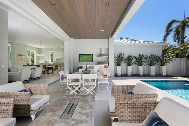 Área gourmet pequena com piscina. Repare na integração dos espaços e na uniformidade da decoração
