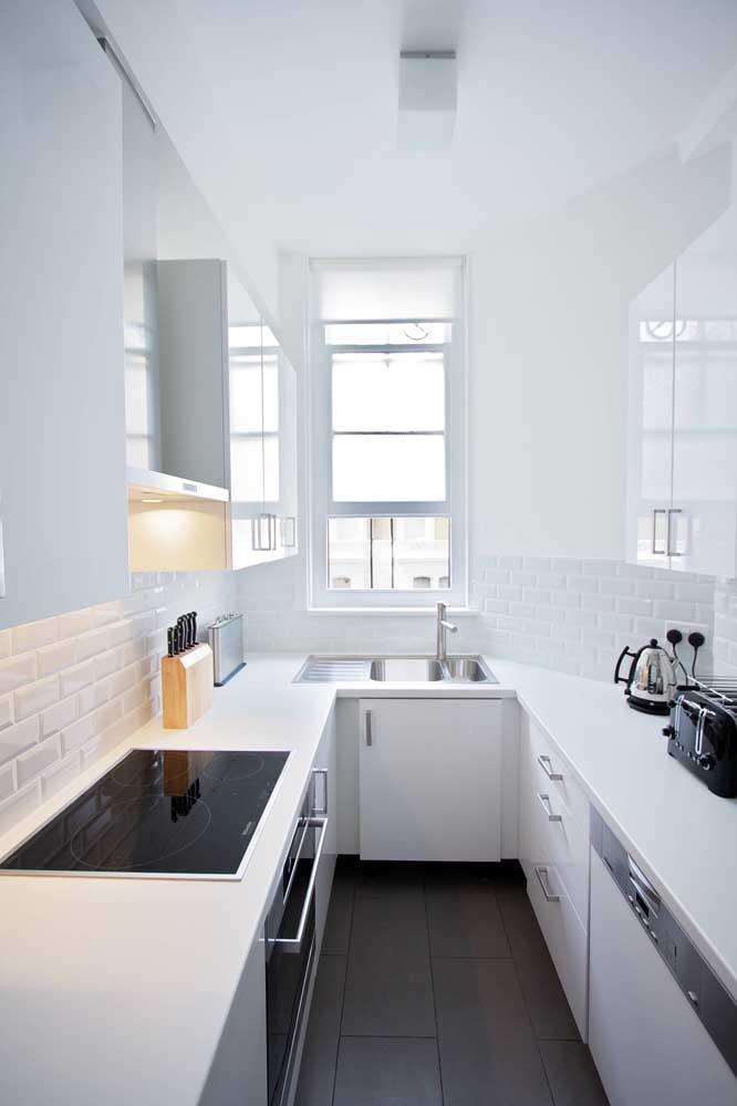 Cozinha em U pequena. As cores claras e o estilo minimalista ajudam a deixar o espaço mais amplo visualmente