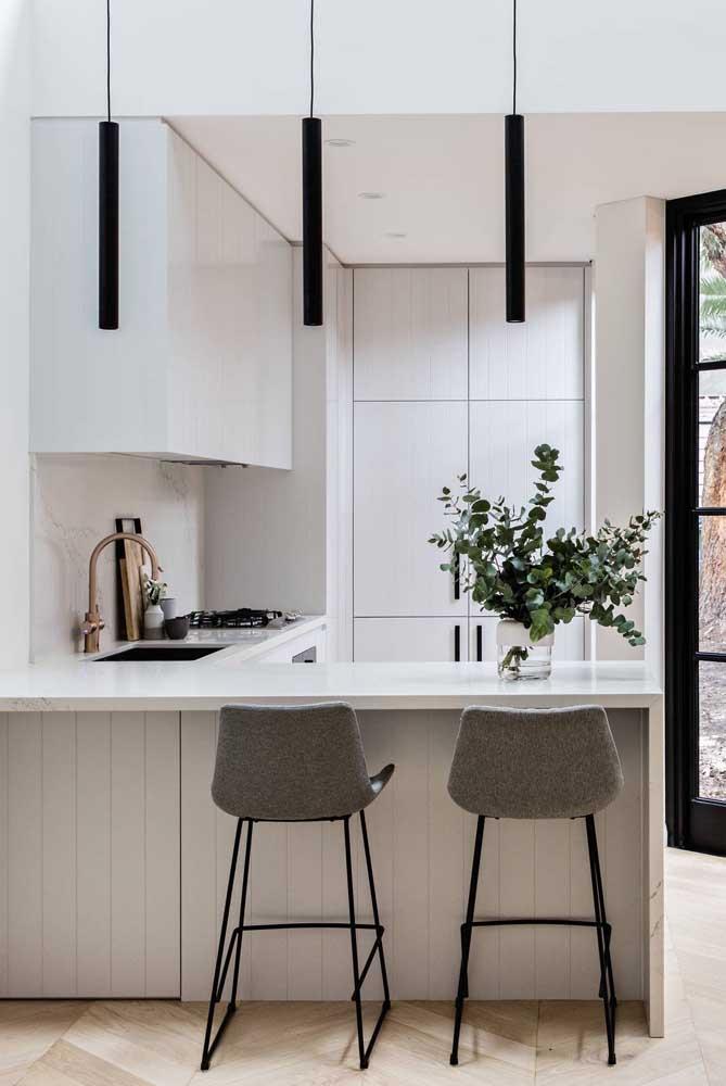 Cozinha em U branca com detalhes pontuais em preto. O resultado é uma composição moderna e elegante