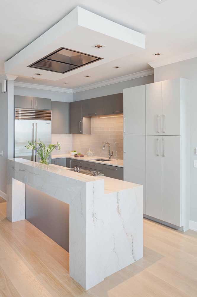 Cozinha em U com bancada. O projeto de iluminação confere elegância e refinamento ao projeto
