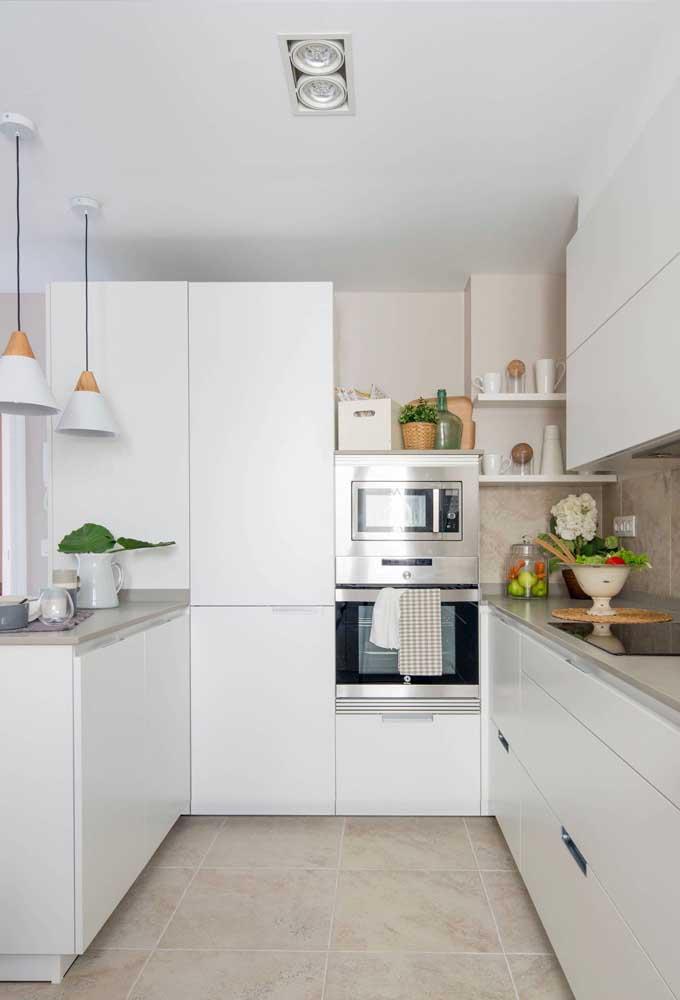 Cozinha em U planejada com bancada. A ausência de puxadores nos armários deixa a cozinha mais moderna