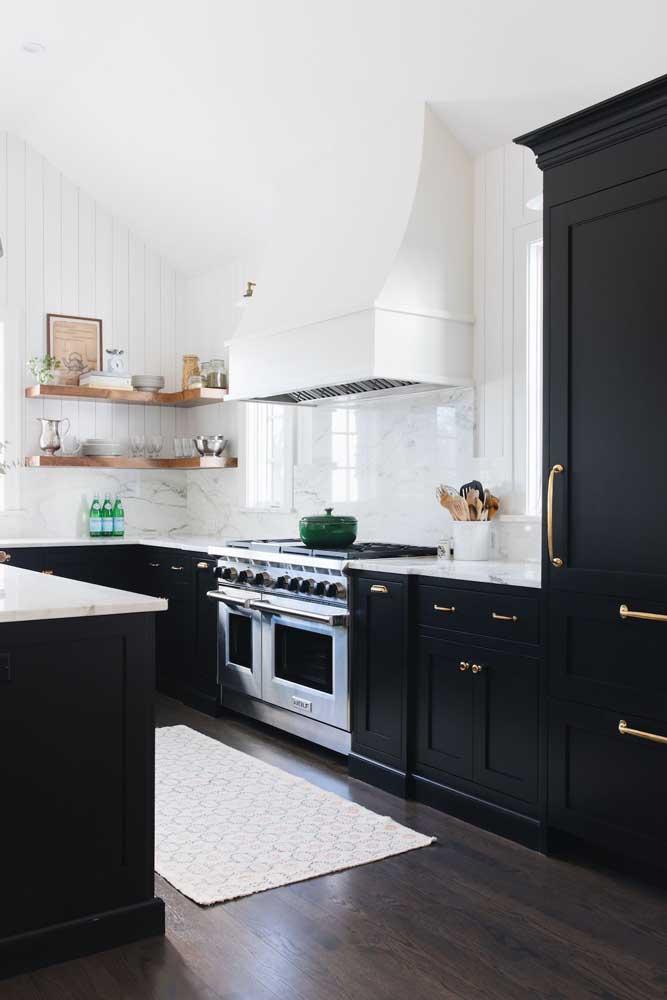 Um luxo essa cozinha em U com armários pretos e puxadores dourados