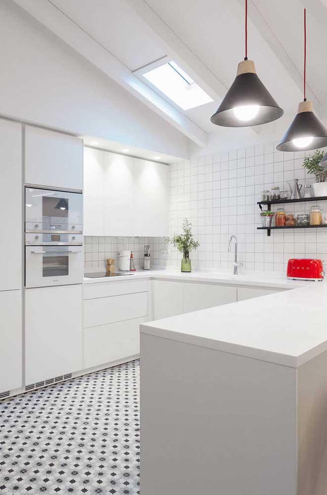 Cozinha em U branca com balcão. As luminárias pendentes garantem um charme a mais ao ambiente