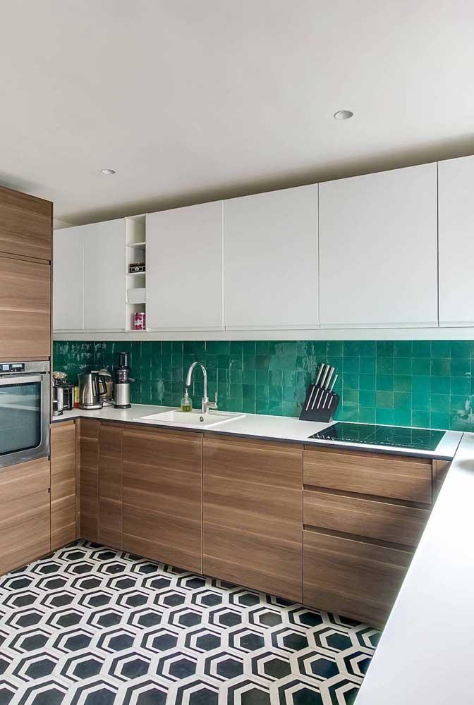 Cozinha em U com móveis planejados em dois tons: branco e amadeirado. Destaque para o piso e o azulejo que garantem cor e vida para o ambiente