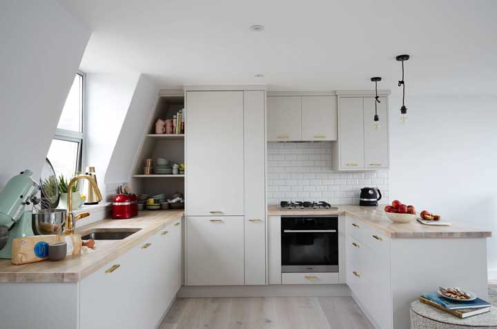Cozinha em U clean. Destaque para o uso da madeira clara combinada aos móveis brancos