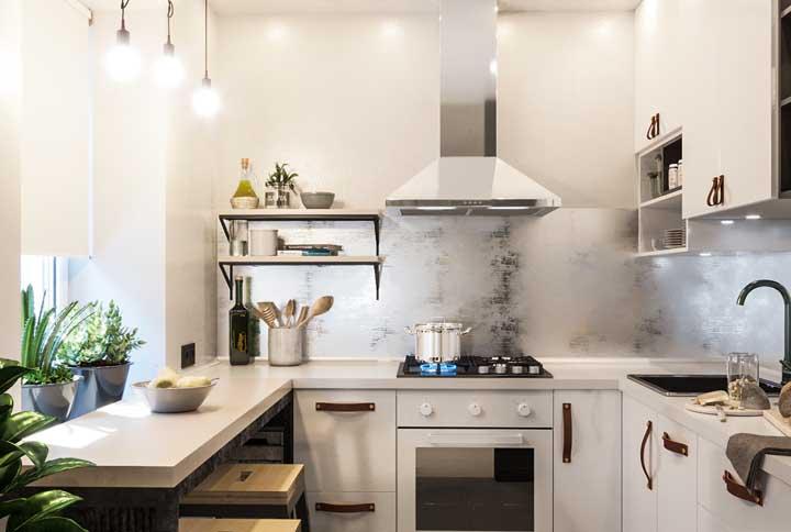 Cozinha em U branca. O charme fica por conta dos puxadores de tira de couro e das plantinhas espalhadas pelo ambiente