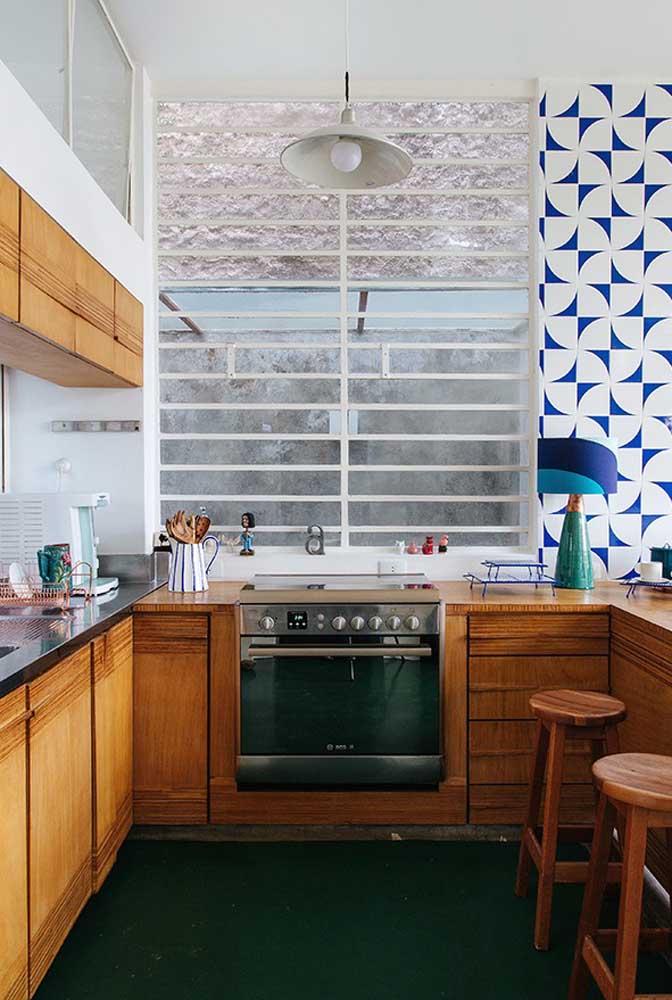 Cozinha em U com móveis de madeira e bancada. O toque vintage é o charme desse ambiente