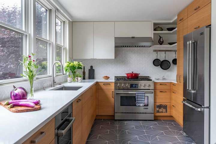 O tom amadeirado dos armários encaixa perfeitamente com os tons de branco e cinza do restante da decoração