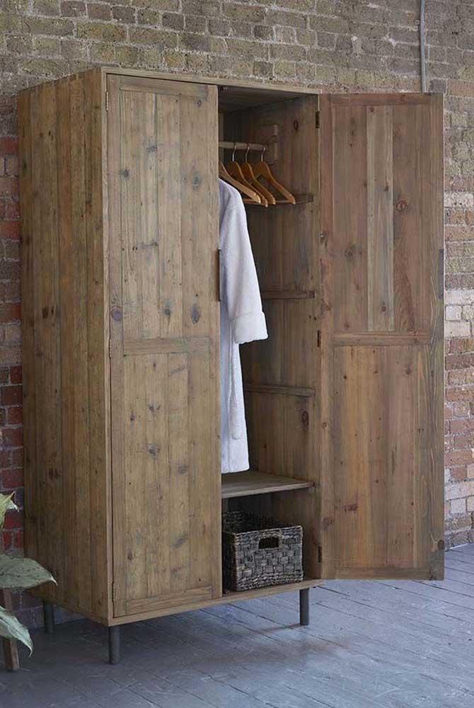 Guarda roupa de pallet com porta casando perfeitamente com a parede rústica de tijolinhos atrás