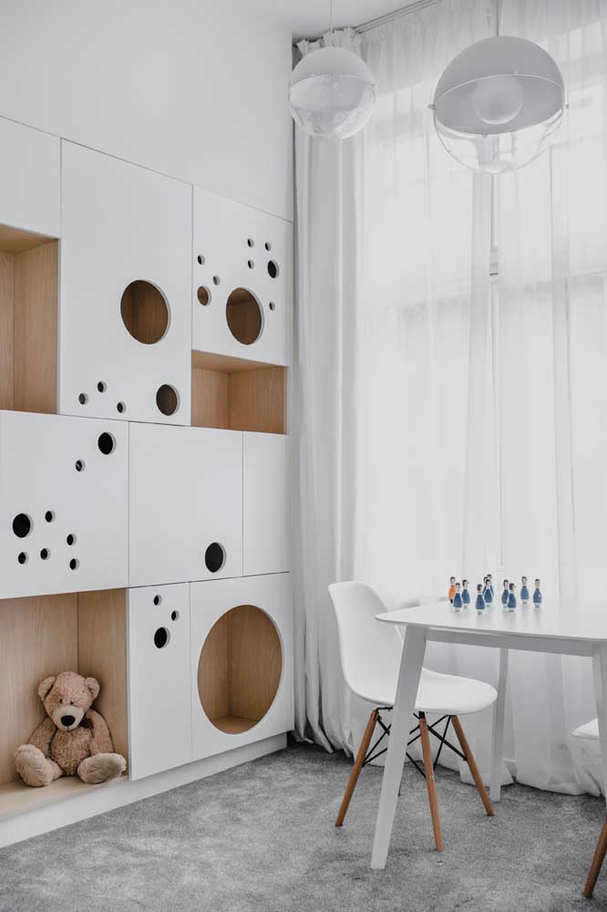 Um armário cheio de nichos que decora e organiza o quarto do bebê ao mesmo tempo
