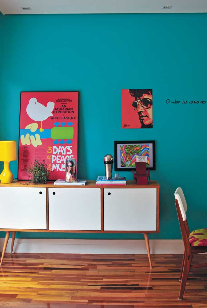 Composição de quadros vintage na sala de jantar. O tom azul esverdeado conferiu ainda mais destaque para os quadros