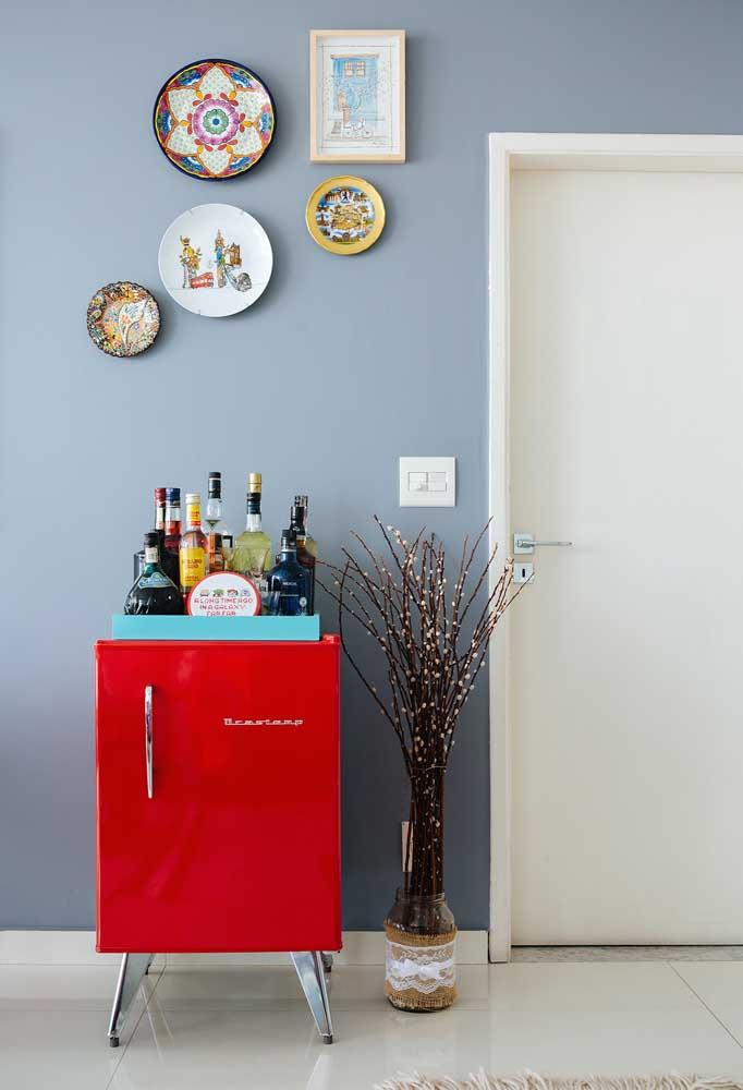 Já aqui, a geladeira retrô faz companhia para a composição de quadros vintage completando a decoração da sala de jantar