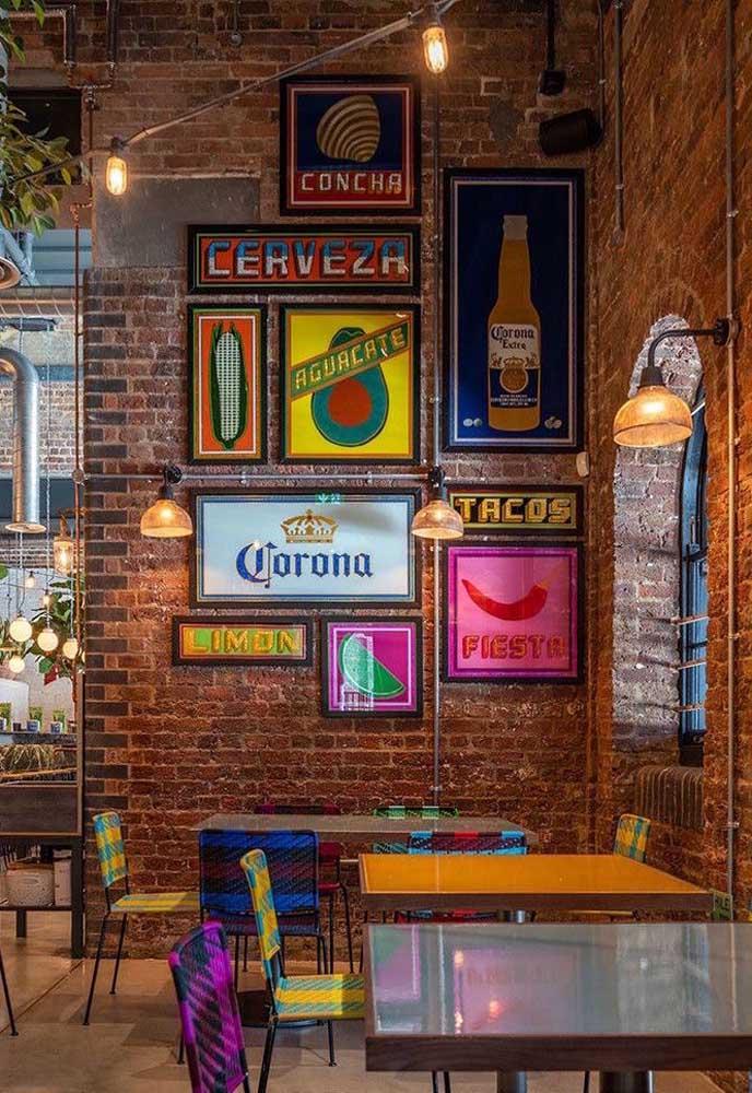 Espaço comercial decorado com quadros vintage de cerveja. A parede de tijolinhos ajuda a criar o clima do local