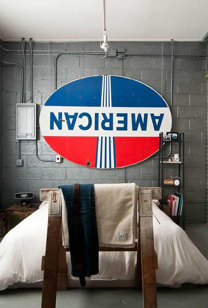 Quarto de estilo industrial com quadro vintage na cabeceira da cama