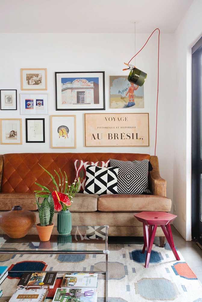 Sala de estar decorada com quadros vintage. Repare que a composição foi colocada na parede principal atrás do sofá