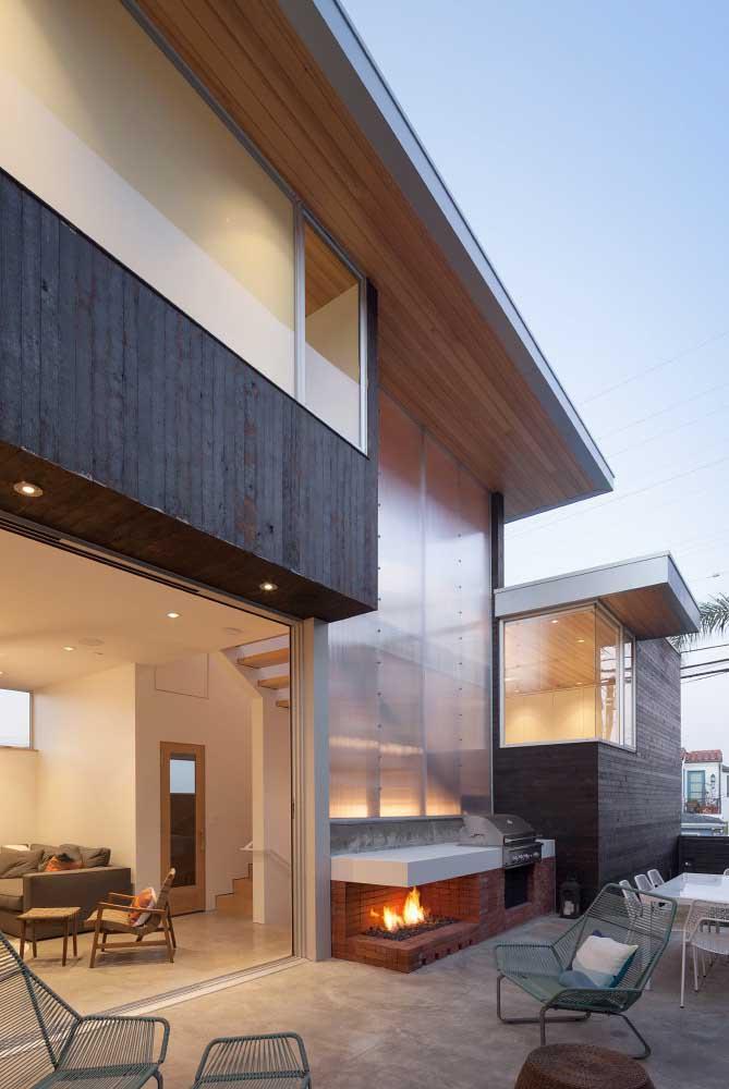 Área de lazer com churrasqueira e forno a lenha no espaço externo da casa