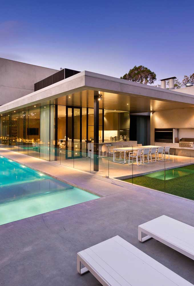 Área de lazer com churrasqueira na parte externa da casa com guarda corpo de vidro delimitando o espaço entre a piscina