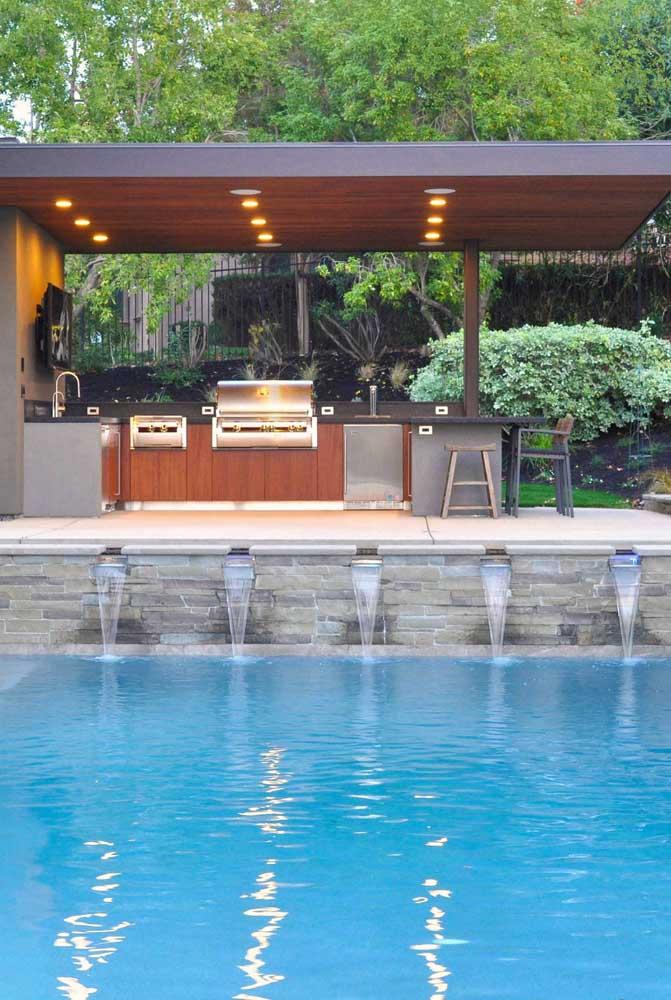Área de lazer com churrasqueira e piscina. Destaque para o jardim aos fundos que integra o ambiente