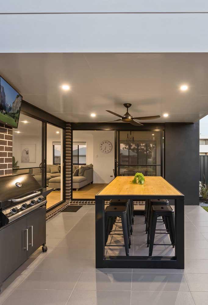 Área de lazer com churrasqueira moderna. Repare que o projeto traz uma mesa mais alta acompanhada de banquetas