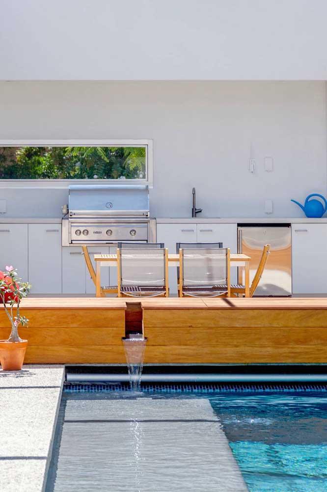 Área de lazer com churrasqueira moderna. As cores claras realçam o estilo moderno e clean do ambiente