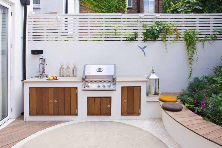 Já aqui, a área de lazer com churrasqueira pequena soube aproveitar o espaço da mureta do jardim para fazer um banco