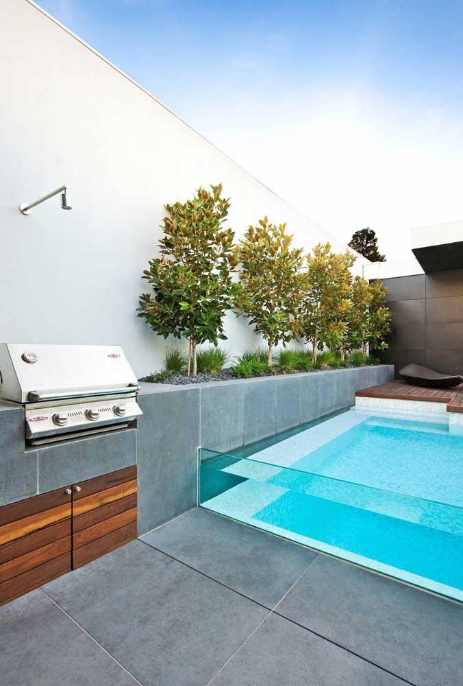 Área de lazer com churrasqueira pequena e simples. A piscina de bordas de vidro é o destaque desse projeto