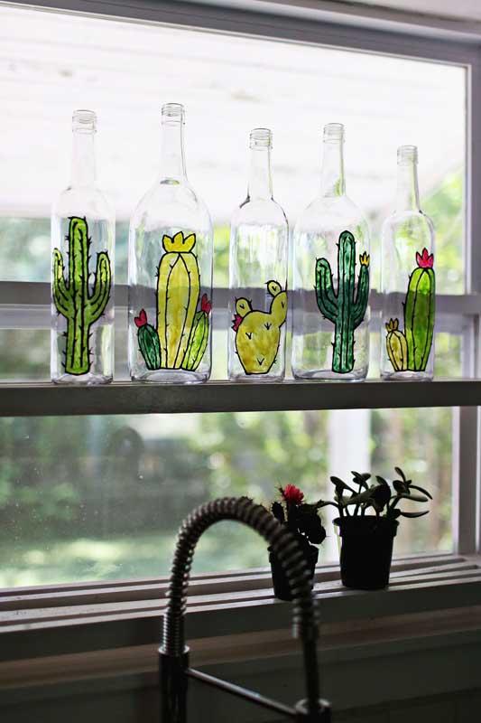 Decoração com garrafas de vidro na janela. O charme fica por conta dos cactos pintados com tinta vitral
