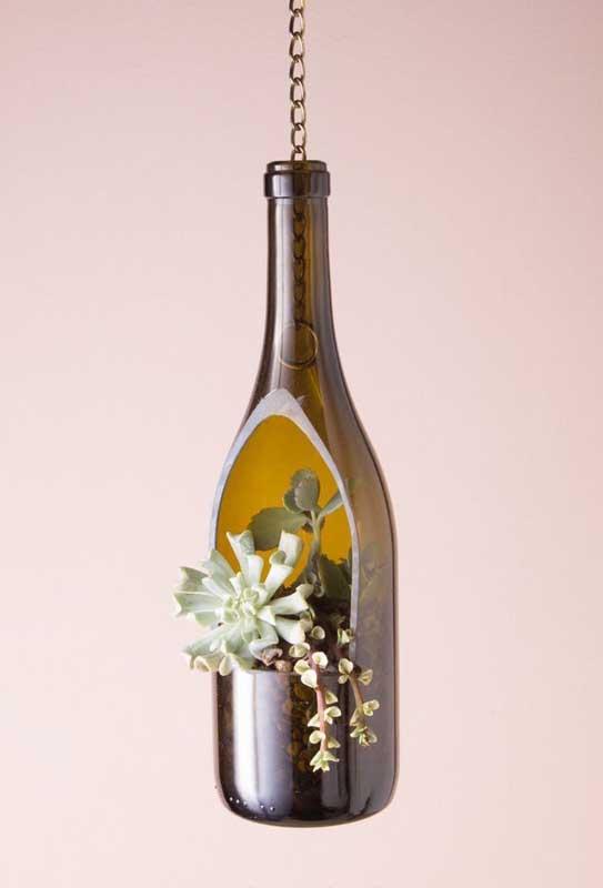 Aqui, a garrafa de vidro suspensa é um lindo vaso para suculentas