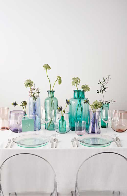 Garrafas de vidro de todas as cores para decorar a mesa da festa