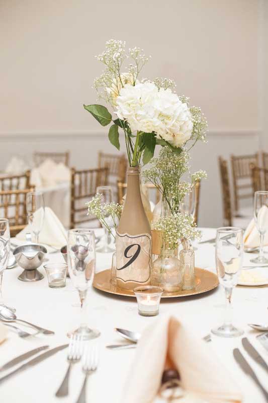 Decoração com garrafas para casamento. Repare que esse centro de mesa foi formado com garrafas de vários tamanhos sobre uma bandeja