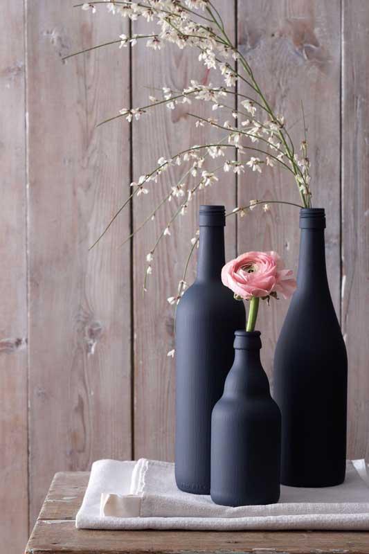 A tinta preta fosca conferiu um ar elegante e moderno para a decoração com garrafas