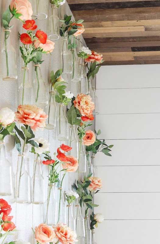 Um lindo e delicado jardim na parede feito com garrafas de vidro e flores